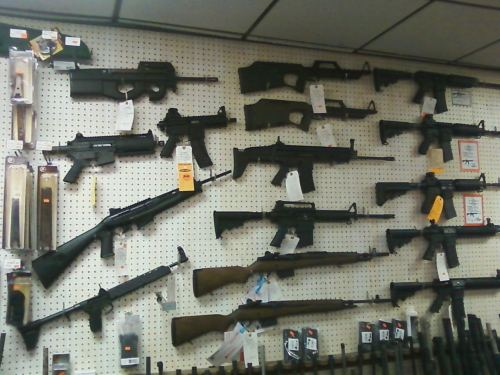 tactical guns hanging on a wall