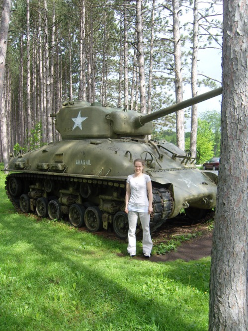 Priscila standing in front of tank
